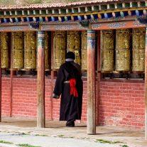 Una pellegrina lungo il 'kora' delle ruote di preghiera